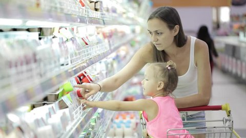 Young attractive woman with cute daughter in shopping cart choosing a yogurt in grocery section at supermarket