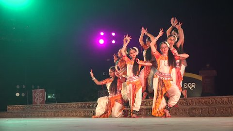 KONARK, INDIA - DECEMBER 2014: An all girl Indian dance group takes on a classic pose during a traditional performance on stage in Konark