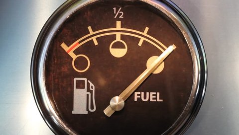 Simulated time lapse of vehicle fuel gauge moving to empty before refueling with moving background visible in reflections.