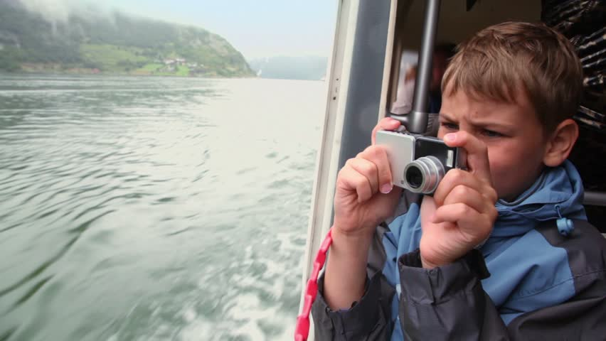 Boy makes photo from rescue boat which floats on fjord with mountains around