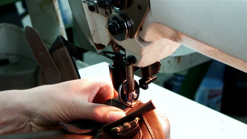 Worker sews leather for shoe production with sewing machine