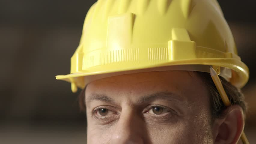 Portrait of happy adult man working as engineer with hardhat in construction site. Slow motion, closeup