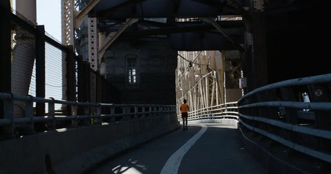 An unrecognizable person runs across New York City's Queensboro Bridge at sunrise. Shot during the summer of 2016 in 4k.