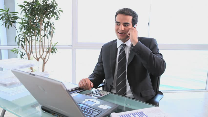 A smiling businessman talking on his mobile phone as he uses the calculator