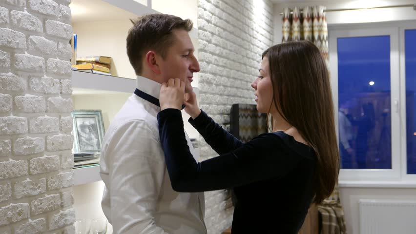 Young woman help her partner with bow tie, put down collar and adjust, give kiss on finish. Cute lovely couple get ready to go out together, formal evening dress, white shirt and dark dress | Shutterstock HD Video #23247544