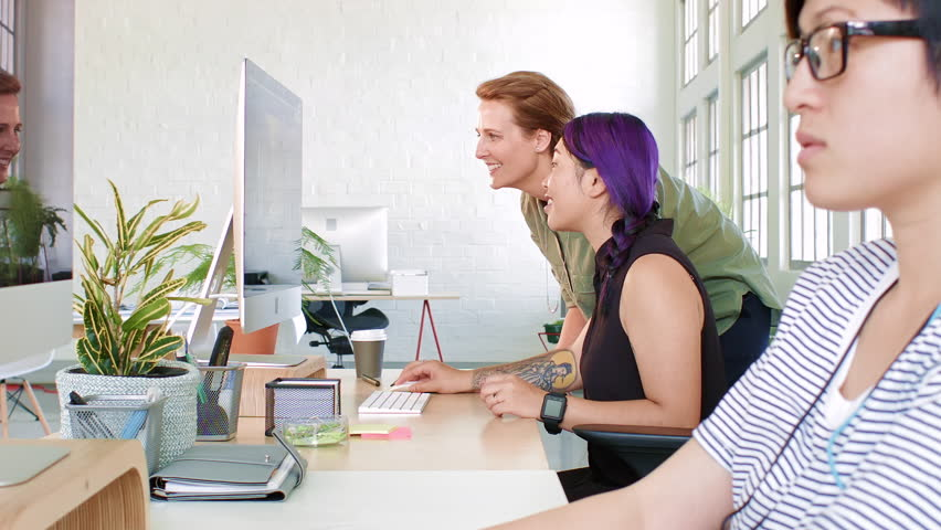 Helpful mentor giving suggestions and ideas to junior designer at her desk workstation | Shutterstock HD Video #23303494