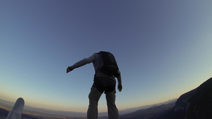 man is jumping from the cliff with green parachute
