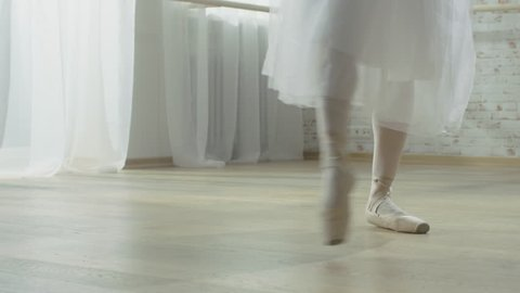 Close-up Shot of Ballerina's Legs. She's Dancing and Spinning on Her Pointe Ballet Shoes. She's Wearing White Tutu Dress. Shot in a Sunny Studio. Shot on RED EPIC-W 8K Helium Cinema Camera.