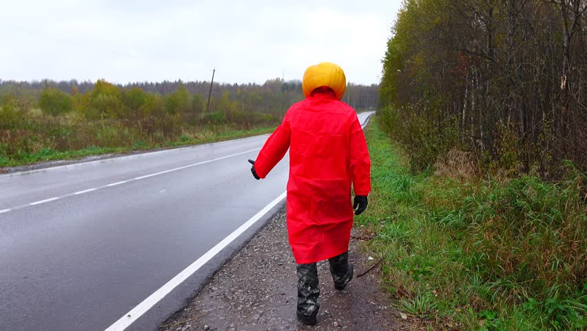 Jack pumpkinhead wear bright red raincoat walk away at roadside and thumbing, then turn face to camera and catch head. Fast truck sweep past, rainy rural outdoors. Halloween prank at countryside
