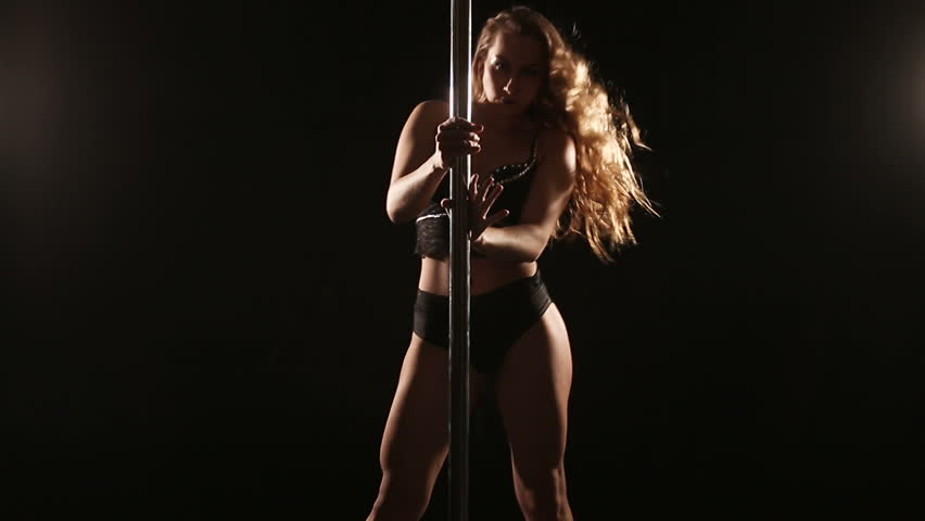 Beautiful slim girl with pylon. Female pole dancer woman dancing on a pole on a black background. Strong and graceful girl dancing on pylon. Girl easily performs complex dance steps on pylon | Shutterstock HD Video #23352214