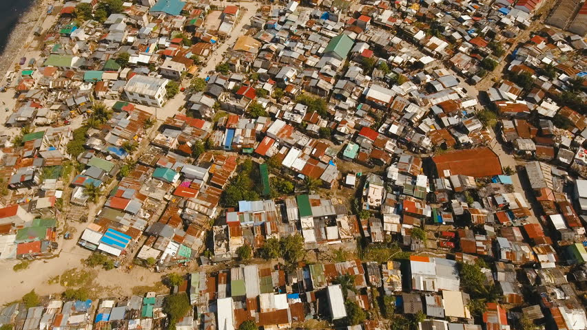 Aerial view poor district of Manila's slums, ghettos, wooden old houses, shacks. Aerial footage slum area of Manila, Philippines. Manila suburb, view from the plane. 4K video.