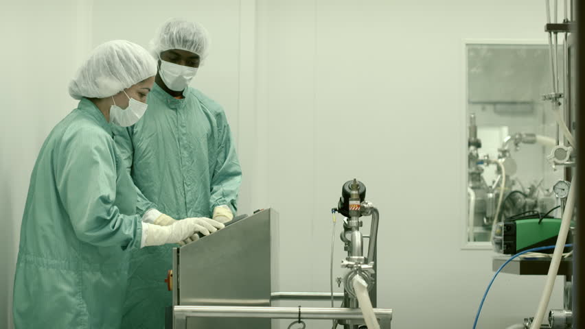 Pharmaceutical industry with people, staff and laboratory technicians at work in medical plant with machinery and computers