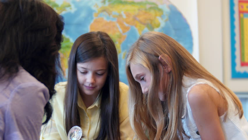 A small group of girls looking at rocks and minerals together with the teacher | Shutterstock HD Video #23387014