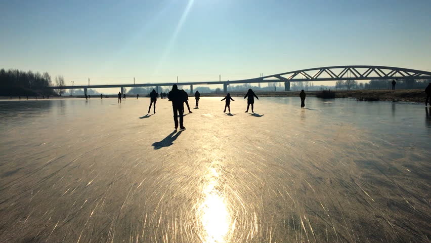 Ice skating people on a frozen lake near the river IJssel in The Netherlands during a beautiful winter day
