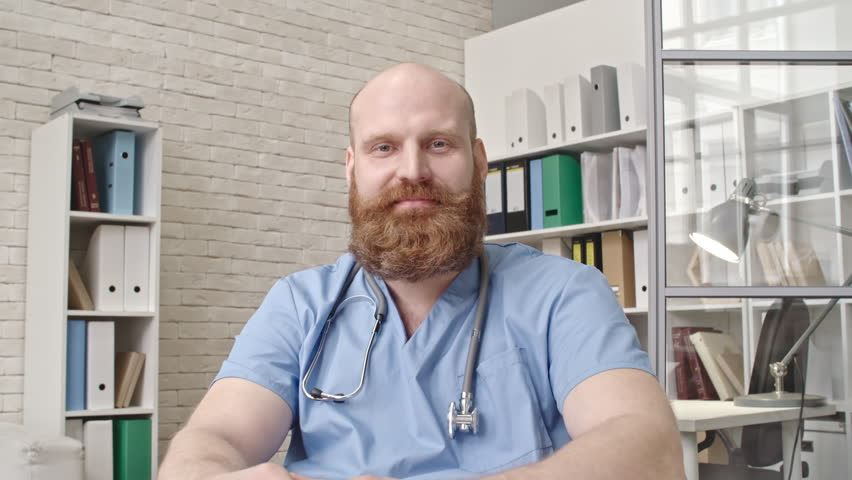 Male doctor giving online consultation via video chat service from his office