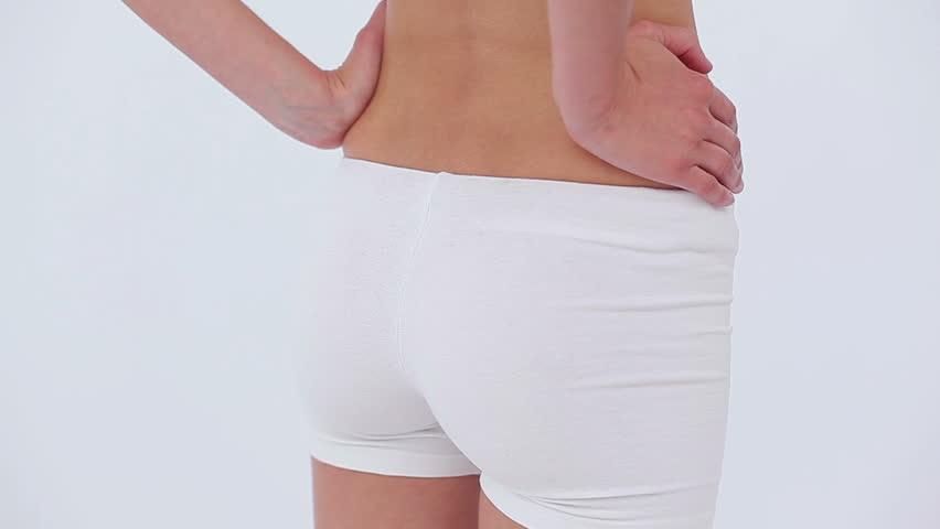 Woman massaging her back against a white background