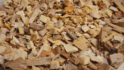 Wood chips for smoking or recycle rotate on the table. Macro shot.