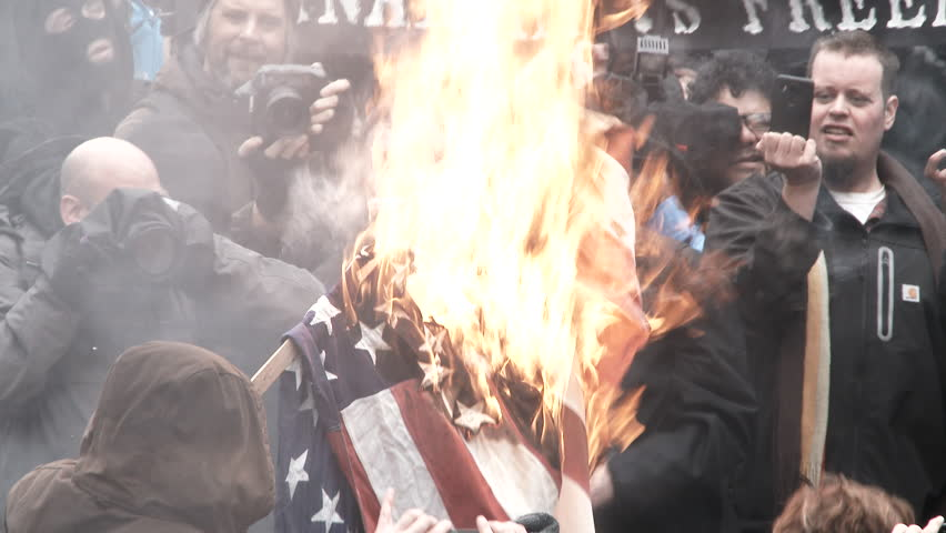 PORTLAND, OREGON - CIRCA 2017: Large group of protesters gather in downtown Portland, Oregon and burn the American flag to demonstrate their first amendment rights against Donald Trump taking office.