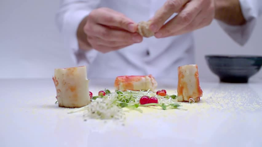 CLOSE UP SLOW MOTION : Chef decorate the dish with crabs, cooked on a white surface