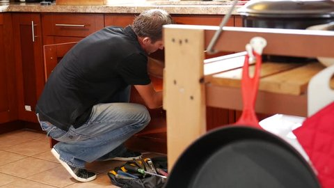 Plumber man with tools in the kitchen. Plumbing and renovation