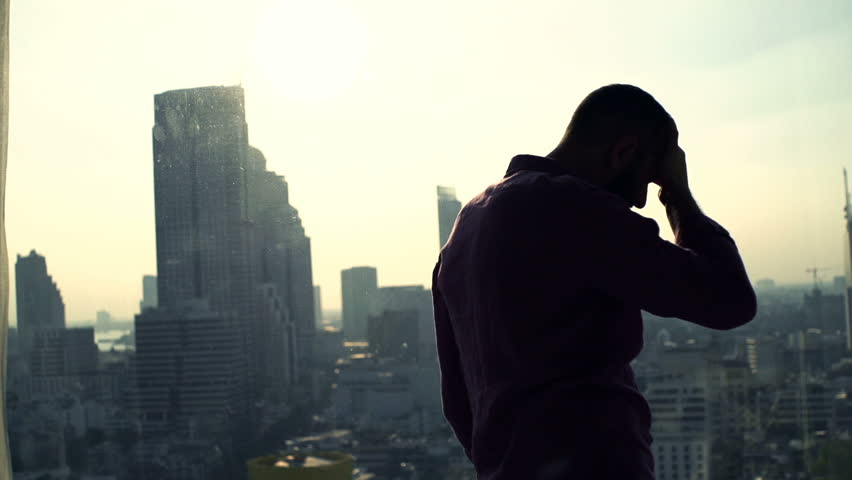 Desperate, sad man standing by window at home  | Shutterstock HD Video #23524924