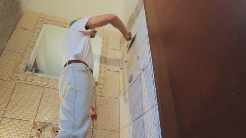man installing tiles in a bathroom hd stock video clip