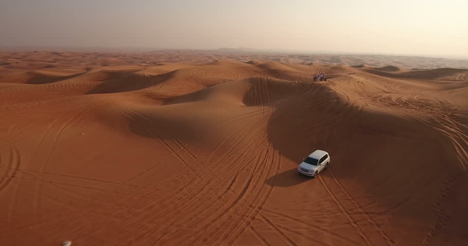 DUBAI, UAE - JANUARY 3, 2017: Aerial view of jeep driving in desert at sunrise. A desert safari is peculiar to Dubai and the UAE. A trip that lasts a couple of hours as you move through the sand dunes #23575444