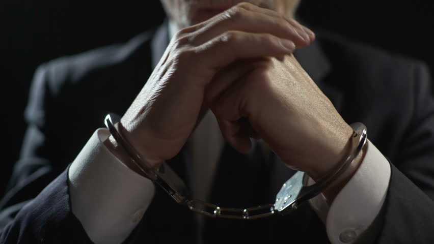 Angry criminal imprisoned in handcuffs, unfair businessman punished for offense