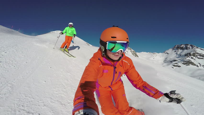 4k skiing footage, woman filming selfie point of view with two skiers following her down ski slope