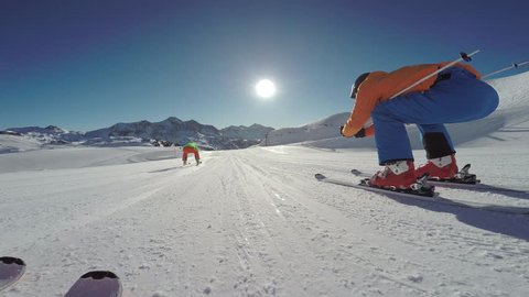4k skiing footage, skier point of view two skiers overtaking on flat ski slope in skiing region