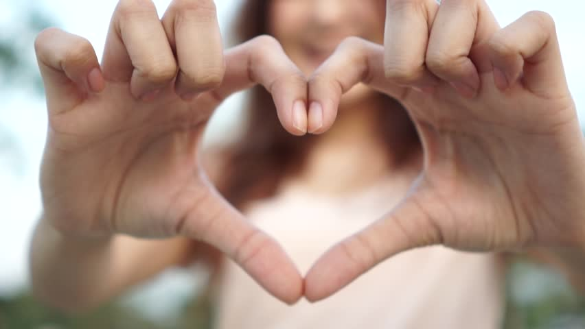 Slow motion : Young woman making heart shape by her hand and smiling