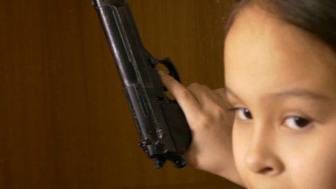 Young child finds gun in closet, points and shoots, gun control concept