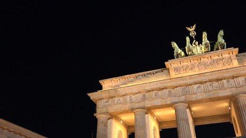 4K Pan right of Brandenburg Gate monument by night, Berlin landmark, illuminated historic emblem