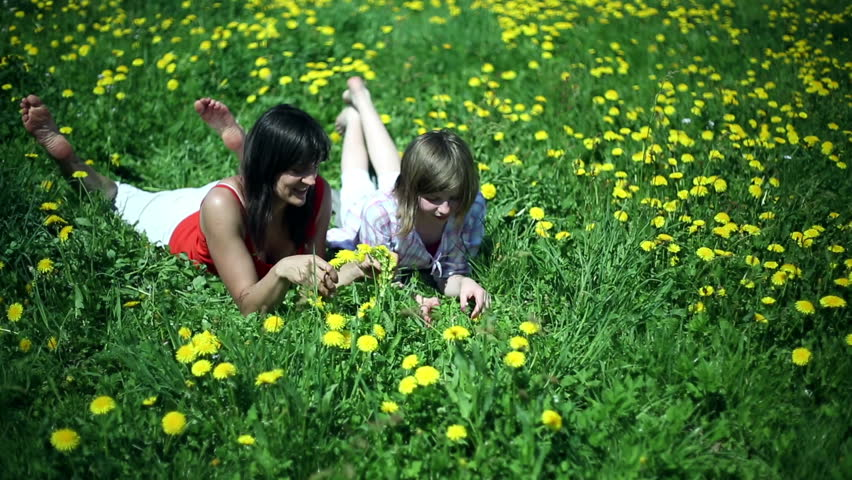 Mother and daughter lying on meadow and making a garland