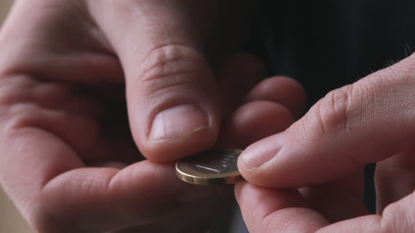 Poor man flipping one last euro coin between fingers and thinking how to spend it, close up of male hand