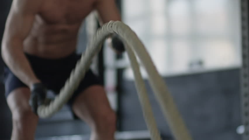Mid-section of unrecognizable shirtless sportsman working out with rope during cross-training routine