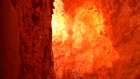 Aluminium foundry furnace loaded with metal. red hot flames glowing and liquid melting