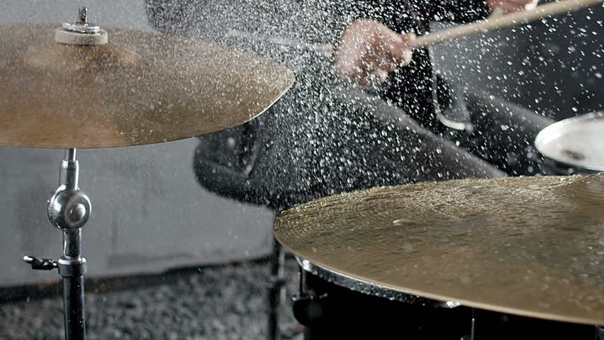 Drummer hitting on wet drum cymbals, and the water splashes from cymbals in slow motion 200 fps. Shot on RED HELIUM Cinema Camera..