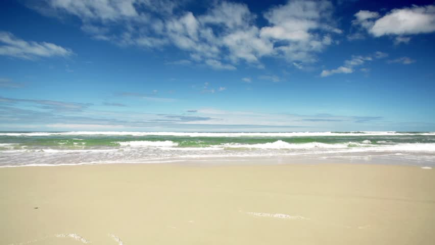 Pristine tropical beach washed by rolling waves, Queensland, Australia. HD