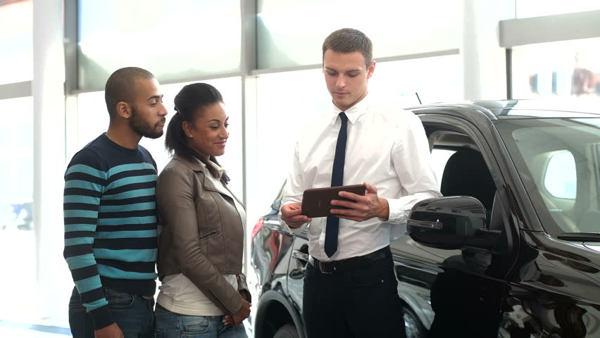 Explaining the Characteristics. Young Handsome Car Seller Using a Digital Tablet to Explain Something to His Customers at the Local Car Dealership