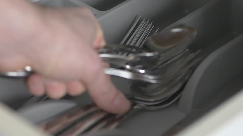 Hand opening a drawer and taking the cutlery out.
