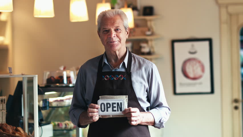 We're Open! Happy Senior Baker Welcoming the Viewer and Customers Smiling Holding an Open Sign in His New Bakery Shop Small Business Owner Seniority Experience Profession Open Happiness Lifestyle