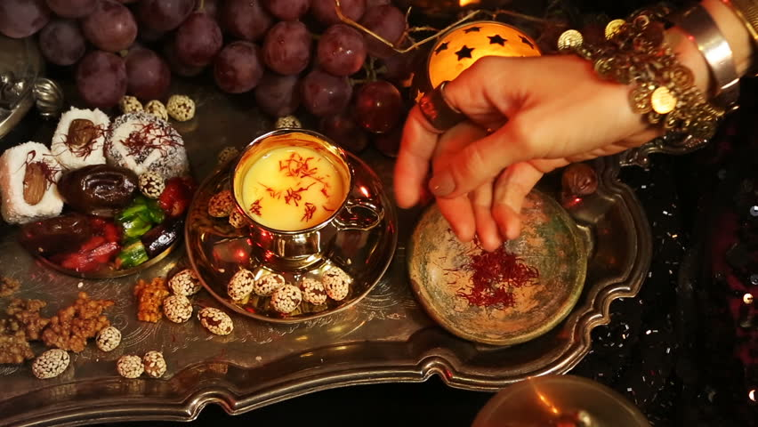 Female hands with beautiful oriental accessories Making Saffron Masala milk Tea with indian spices. Traditional Moroccan Sweets. Gala dinner by candlelight. Arab, Turkish, Persian and Indian dishes