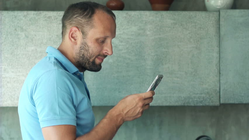 Young man using smartphone in the kitchen, 4K  | Shutterstock HD Video #23716744