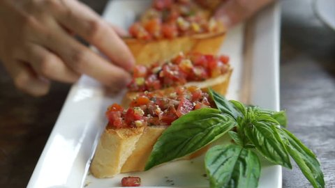 Hands taking yummy bruschetta and fresh basil leaves to eat