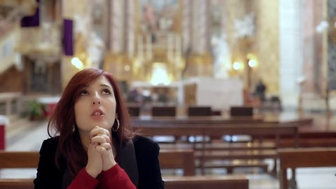 Believing woman kneeling in church prays