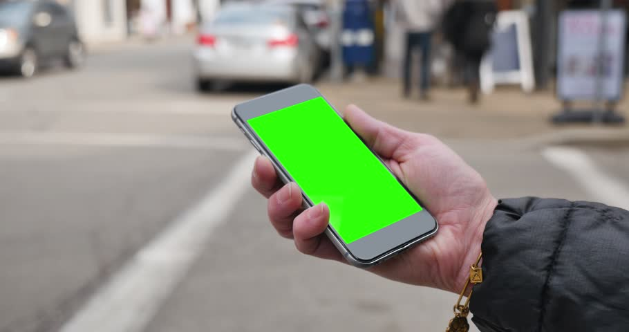 A woman holding a green screen smartphone in a city. Green screen with optional corner pin points for advanced tracking and screen replacement.