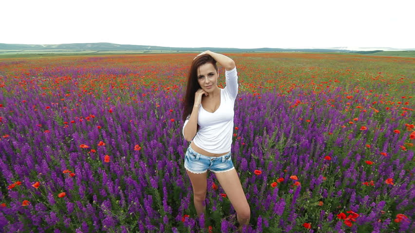 Attractive young woman posing in blossoming field