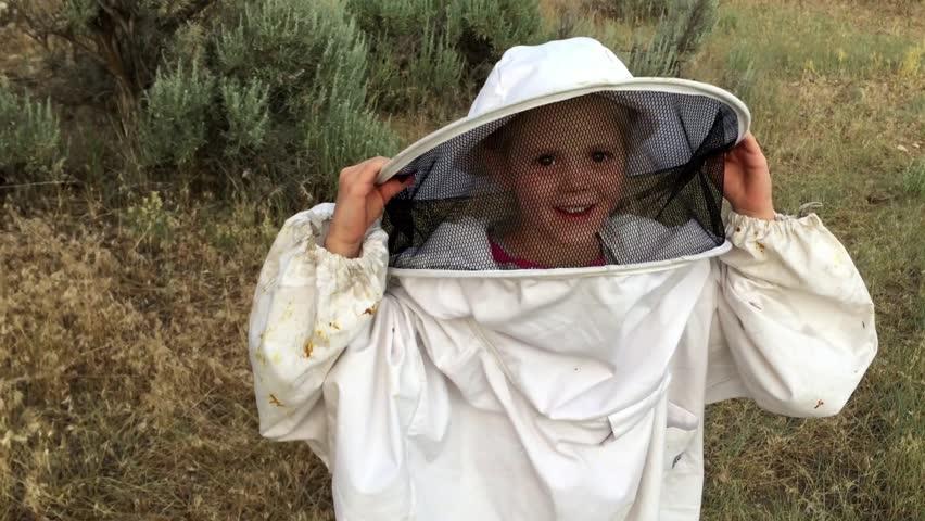 A little girl wears an oversized bee suit.