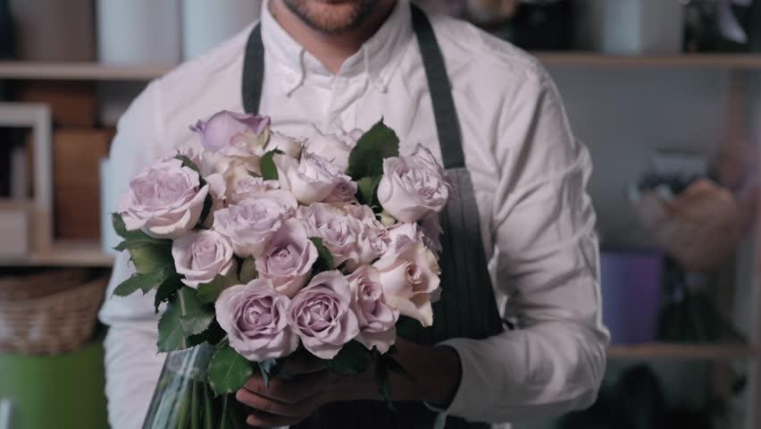 Close up florist hands. man making bunch at flower shop. people, business, sale